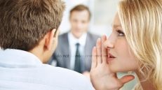 Woman whispering in the ears of the business man with their leader in background