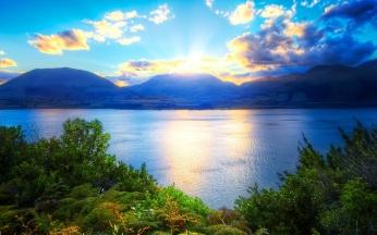 mountains_sun_light_clouds_vegetation_lake_bushes_green_fern_trees_62310_2560x1600